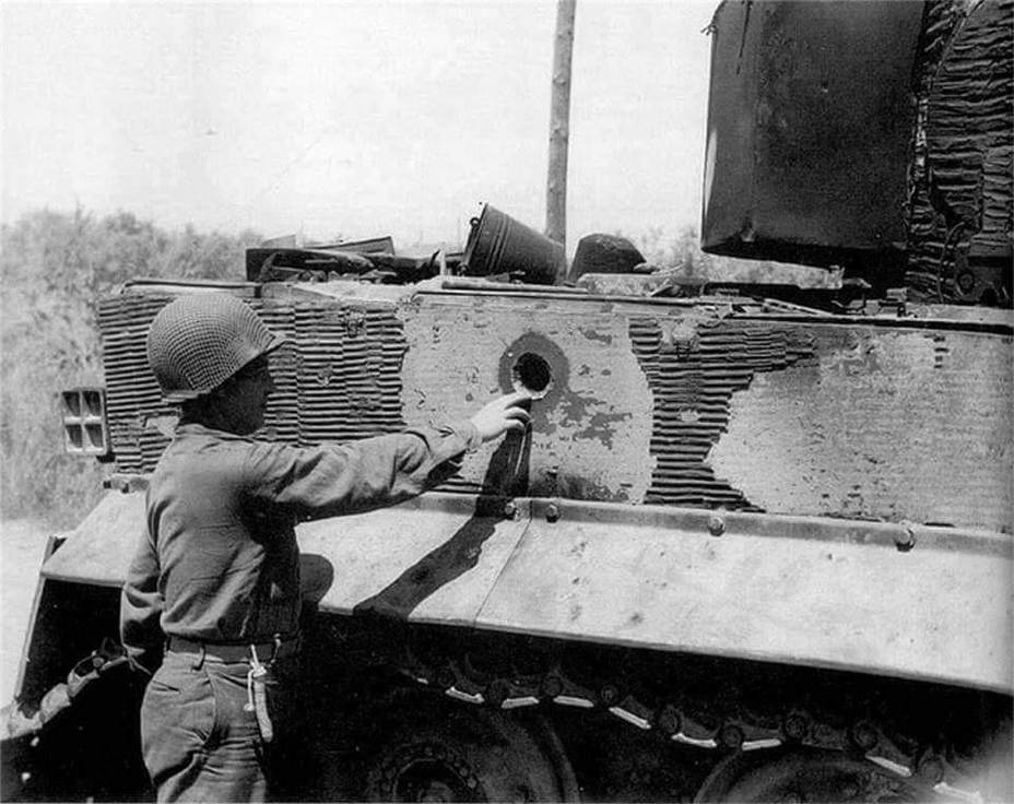 ​An American soldier inspecting a hole in the side of a Tiger tank. Despite their thick armour, they were far from invincible - Tiger Killers | Warspot.net