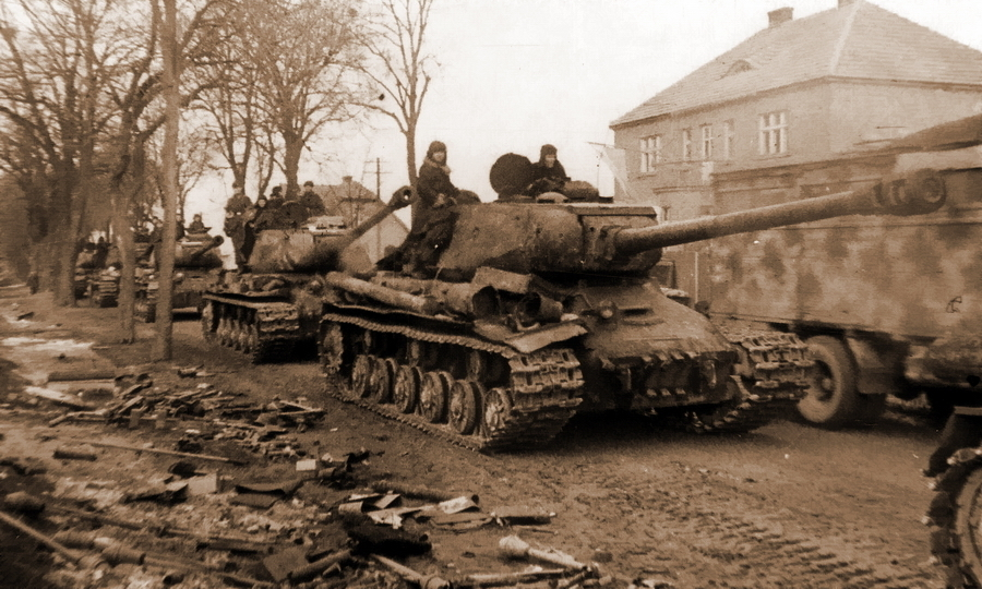 ​IS-2 heavy tank convoy moving through a town somewhere in East Prussia. Faustpatrones on the side of a road do not pose danger to the troops anymore - «Panzerfäust almighty» | Warspot.net