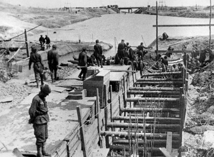 ​A photo has survived in which soldiers of 10th Division of the internal troops of the NKVD are building the dugout of the division headquarters. In this dugout, the command post of 92nd OSBR was located. In the distance you can see the bridge and railway running along the banks of the Volga - Unknown Stalingrad: The City Garden | Warspot.net